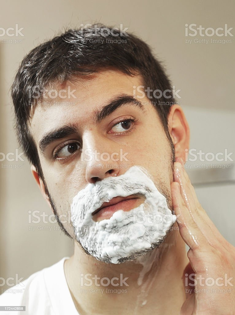 Young Man Checking Shaving Progress in Mirror royalty-free stock photo