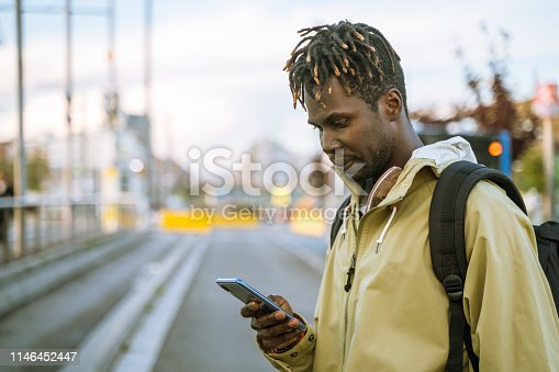 Casual young man checking mobile phone at a Barcelona street.