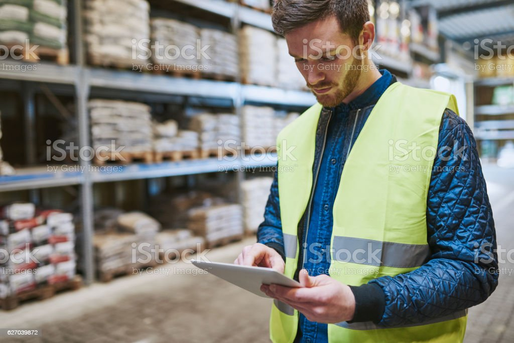 Young man checking supplies on his tablet Young man shopping or working in a hardware warehouse standing checking supplies on his tablet with an absorbed expression Adult Stock Photo