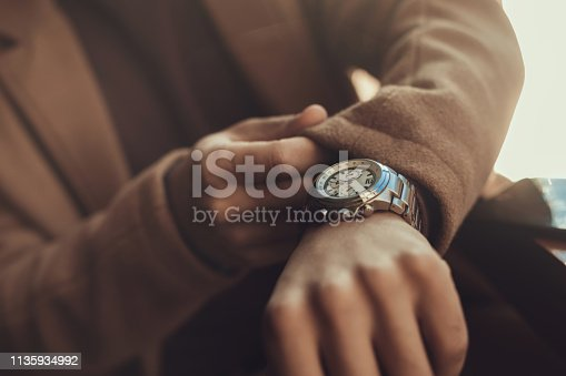 istock Young man checking time on his elegant wristwatch 1135934992