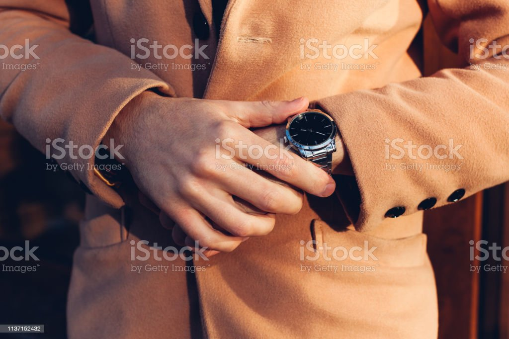 Young man checking time on stylish metal mechanical hand watch...