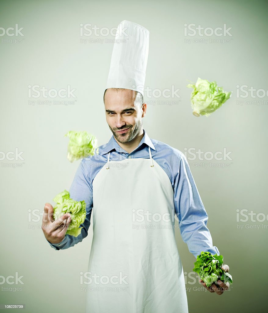 Young Man Chef juggling lettuce heads stock photo