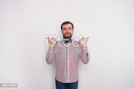 istock Young man choosing between two options concept. He is confident and points to different sides by his thumbs. 936120552