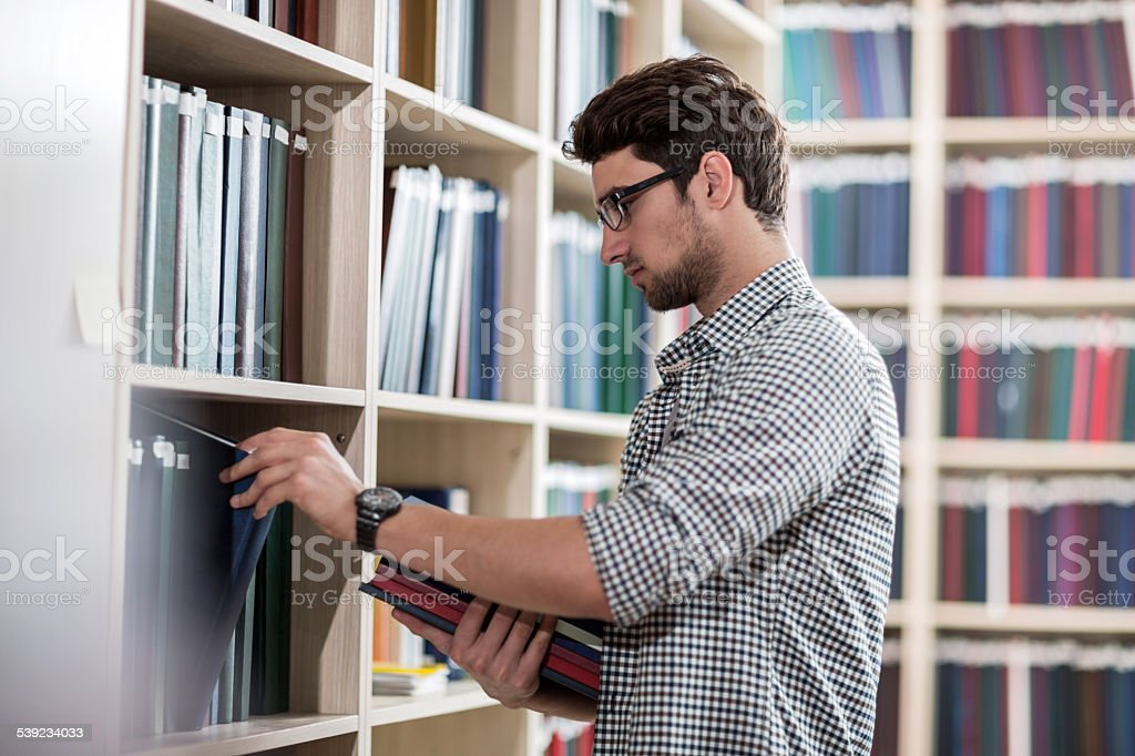 Joven eligiendo libro en la biblioteca. foto de stock libre de derechos