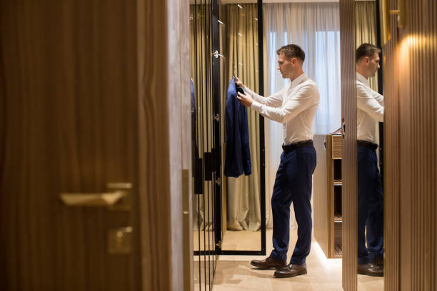 Young man choosing clothes from  wardrobe in the hall of contemporary apartment stock photo