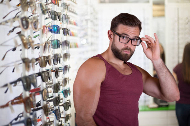 Young man choosing glasses stock photo