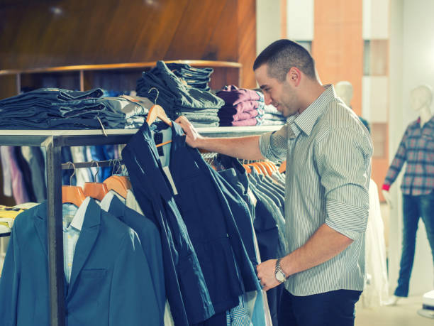 Young man choosing suit in clothes store stock photo