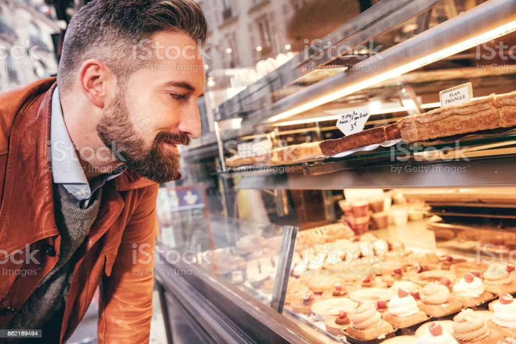 Young man choosing sweets in Paris, France stock photo