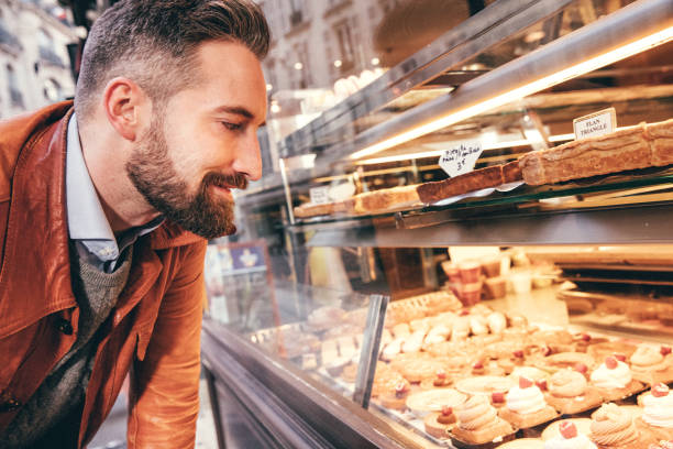 Young man choosing sweets in Paris, France Young man choosing sweets in Paris, France temptation stock pictures, royalty-free photos & images