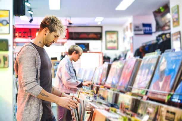 Young Man Choosing Vintage Vinyl LP In Records Shop stock photo
