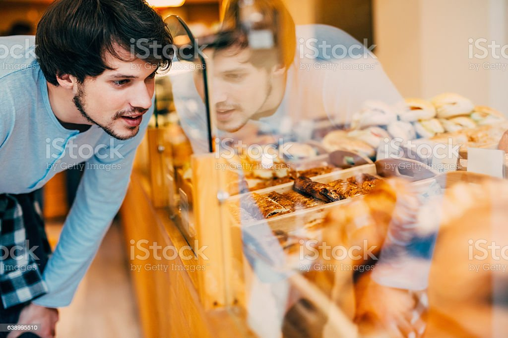 Young man choosing what to buy at a bakery - Photo
