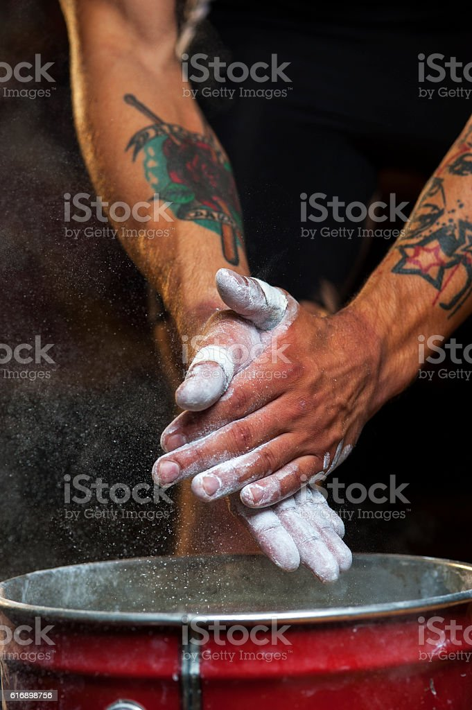 Young man clapping hands with talc powder stock photo