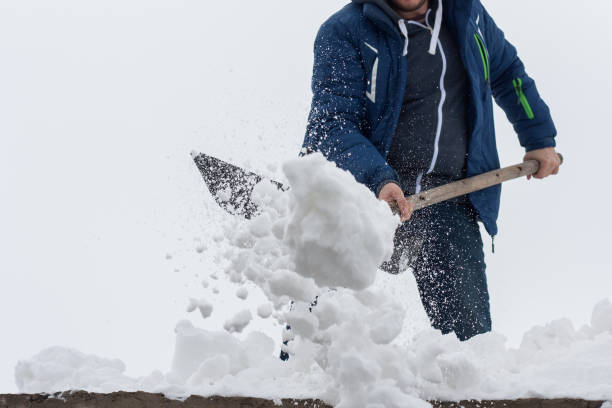 Young man clean a roof from snow by shovel. Spring snow removing after blizzard. stock photo