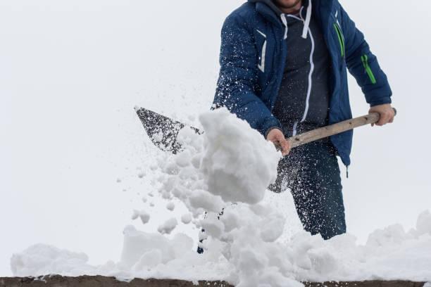 junger mann reinigen ein dach vom schnee schaufel. frühling schnee entfernen nach blizzard. - entfernt stock-fotos und bilder