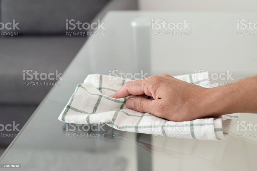 young man cleaning a glass table stock photo
