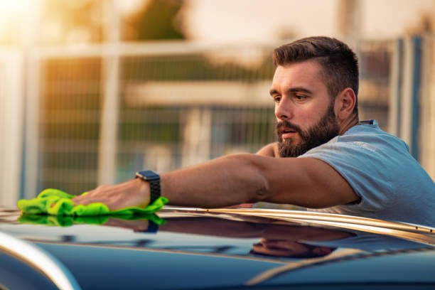 Young man cleaning his car outside stock photo