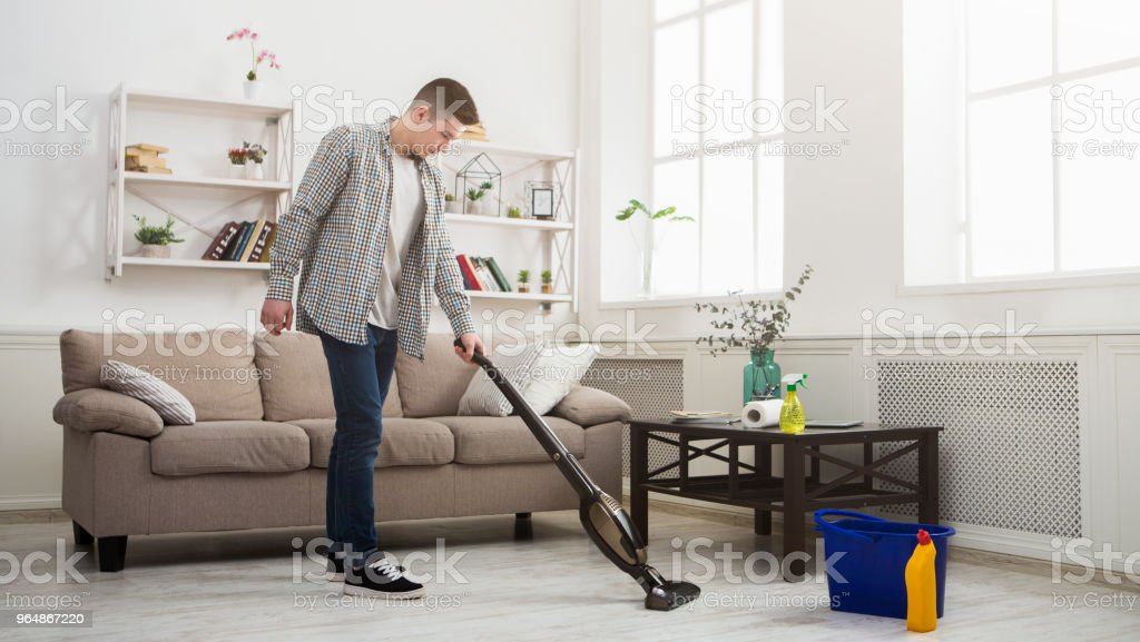 Young man cleaning house with vacuum cleaner royalty-free stock photo