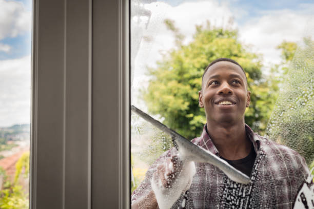 Young man cleaning patio door windows stock photo