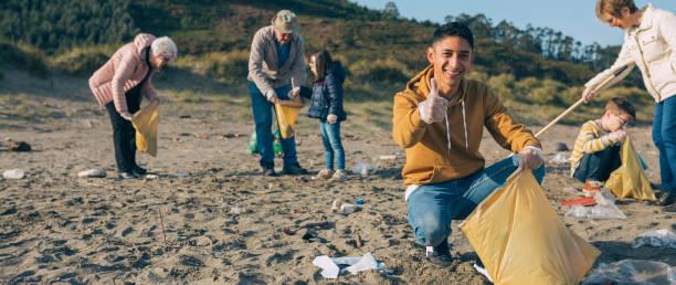 Junger Mann putzt den Strand – Foto