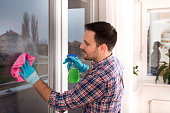 Handsome young man cleaning windows with cloth and spray bottle at home