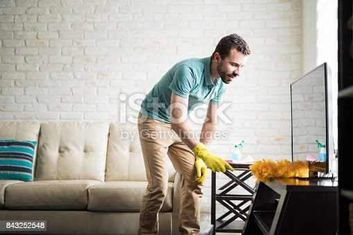 Attractive Latin man in his 30s doing house chores to maintain his apartment clean