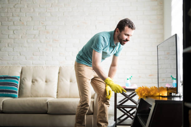 Young man cleaning with a duster stock photo