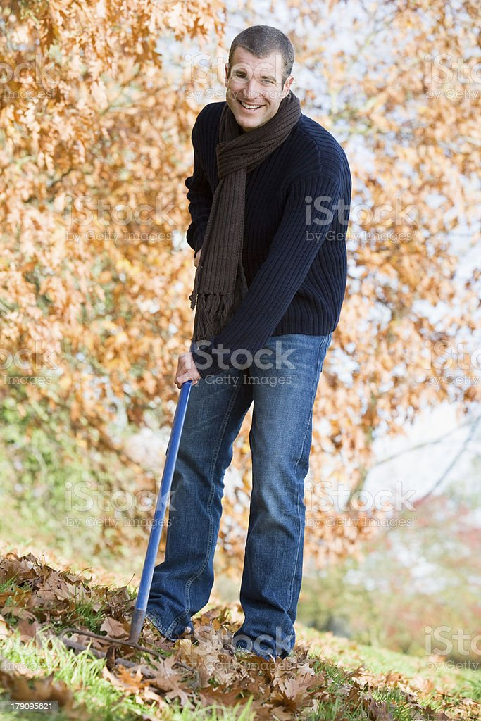 Young man clearing autumn leaves royalty-free stock photo