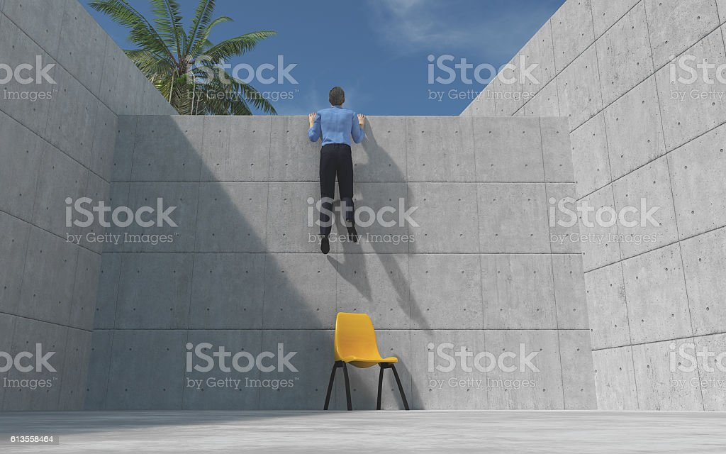 Young man climbed a concrete wal stock photo