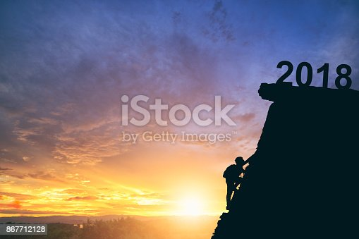 istock Young man climbing between 2017 and 2018 years. Happy new years concept 867712128