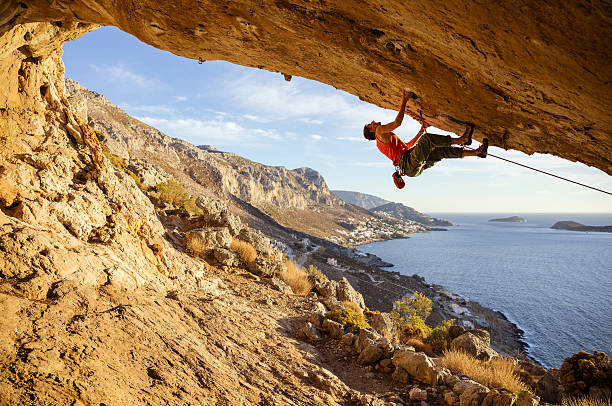 Young man climbing in cave stock photo