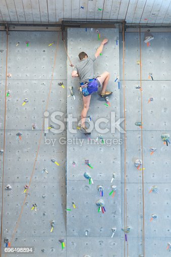 Young man climbing indoor rock wall using harness and rope equipment