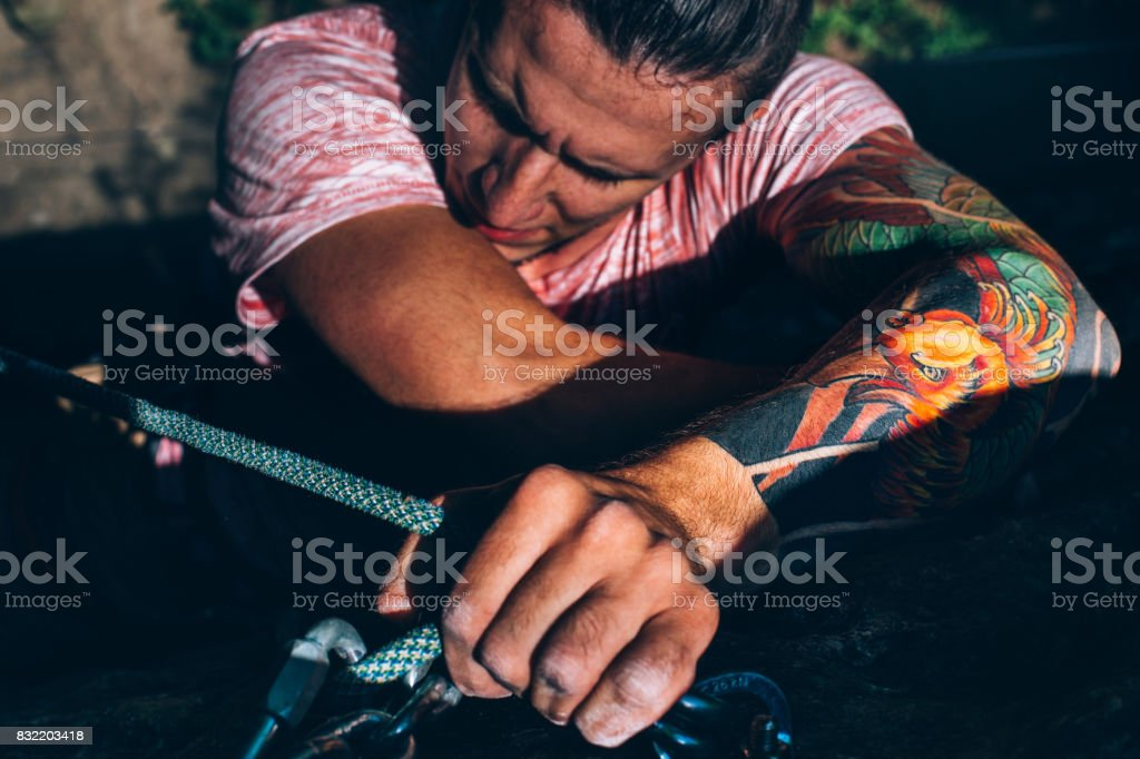 Young Man Climbing On The Rock Wall, Close-up Of Male Hands With Tape In Magnesium Powder stock photo