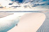 Young man climbing the sand dunes of Lençois Maranhenses