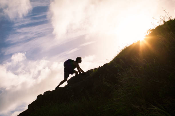 Young man climbing up a mountain. stock photo