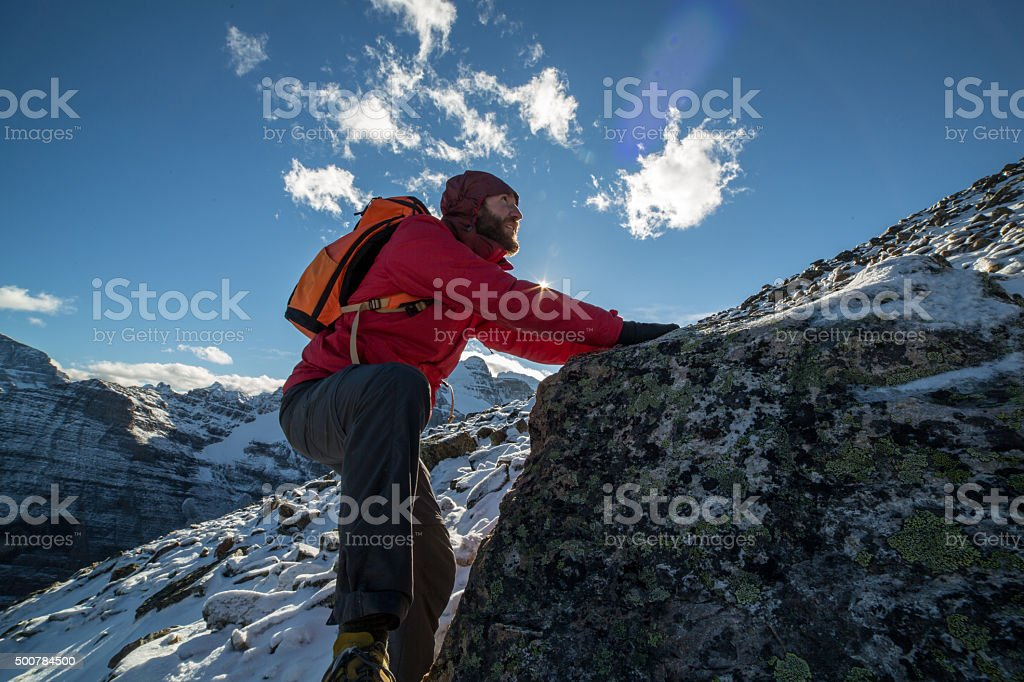 Young man climbs steep rock, moving up. Low angle view.