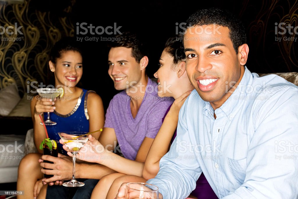 Young Man Clubbing With Friends Enjoying Cocktail Drinks royalty-free stock photo