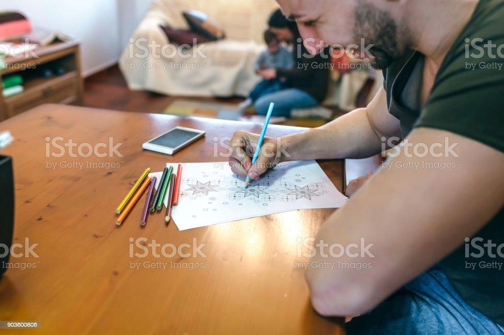 Young man coloring mandalas stock photo