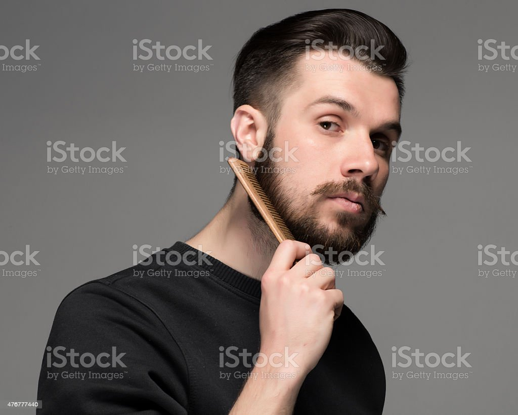 young man comb his beard and moustache stock photo