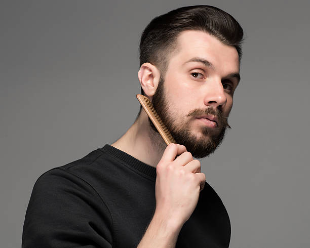 young man comb his beard and moustache young man comb his beard and moustache on gray background combing stock pictures, royalty-free photos & images