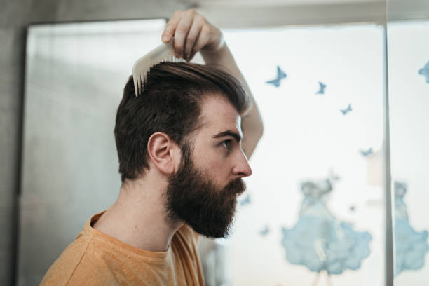 Young man combing hair in the bathroom stock photo