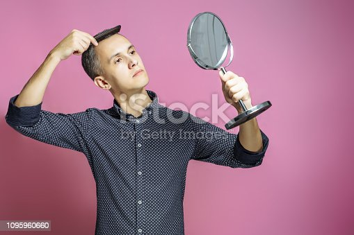 istock Young man combing his hair in front of a mirror on a pink background. 1095960660