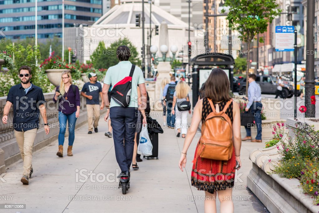 Young man commuting home in Chicago on a scooter stock photo