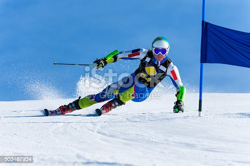 Front view of young skier at giant slalom race; at the blue gate