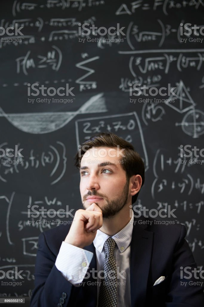 Young man contemplaiting in front of blackboard stock photo