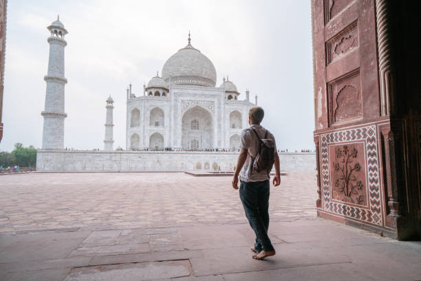 Young man contemplating the famous Taj Mahal at sunset stock photo