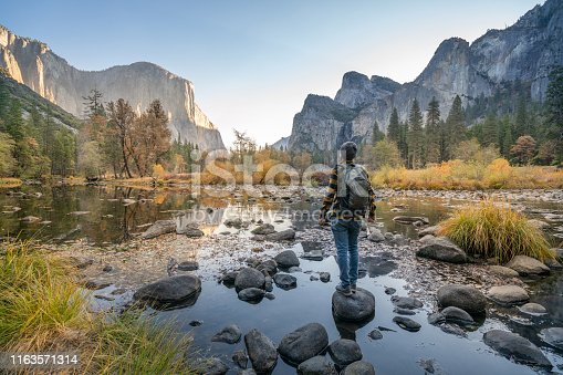 Young man contemplating Yosemite valley from the river, USA