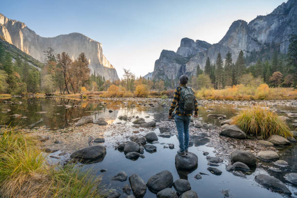 Young man contemplating Yosemite valley from the river, reflections on water surface stock photo