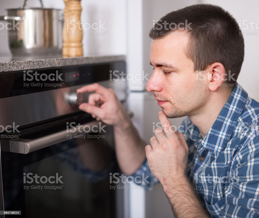 young man controls the oven in kitchen – Foto