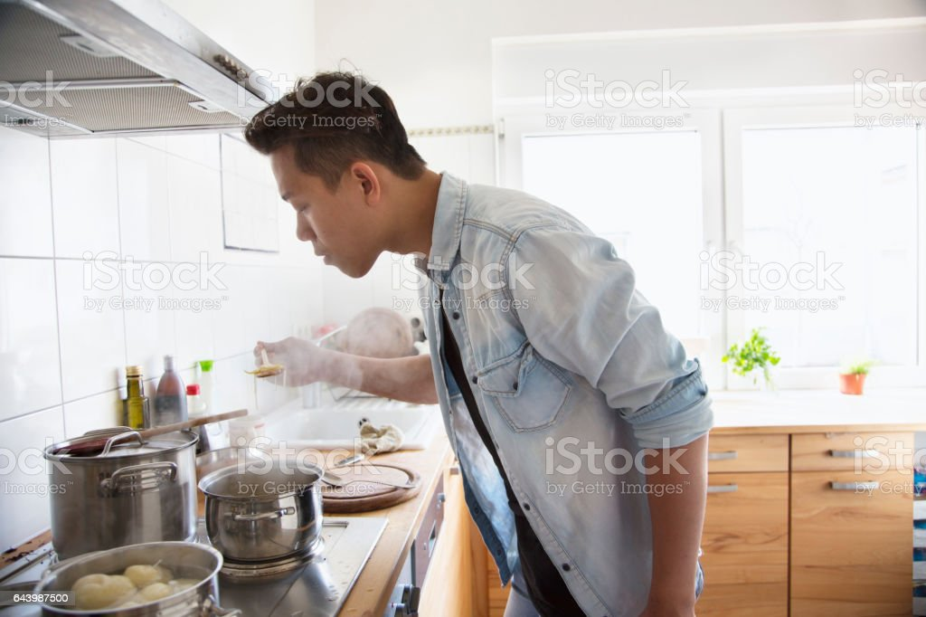 Young man cooking in the kitchen stock photo