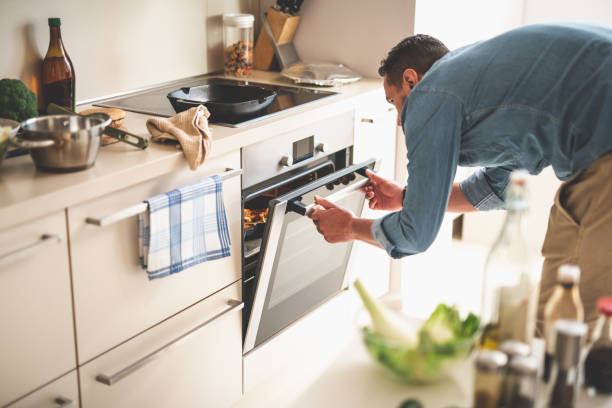 Young man cooking meat in oven at home stock photo